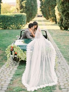 Obsessing over this wedding photo. A gorgeous train drapes over a vintage car for a whimsical yet romantic look.