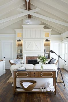 I am in love with the barn doors above the fireplace. It would hide a TV nicely. I would put these doors on slides to tuck them back into the cabinet when open