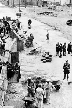 East German construction workers, supervised by border guards, building the Berlin Wall, 1961.