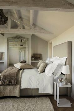Elegant French inspired bedroom with mushroom linen headboard bed, pebble rug, French floor mirror, white nesting tables nightstands and wood baluster lamps.