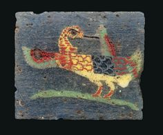 AN EGYPTIAN MOSAIC GLASS WATER FOWL INLAY   PTOLEMAIC-ROMAN PERIOD, CIRCA 1ST CENTURY B.C.-1ST CENTURY A.D.   Possibly a snipe, the head turned backwards with long brown beak, red and yellow, then blue and white, then green and red imbricated covert feathers, with green and yellow fan tail, preening its left wing, red, dark brown and green flight feathers, with yellow underbelly and red striped feet on green base line, in translucent grey-blue matrix  1 in. x 13/16 in. (2.5 cm. x 2.1 cm.)