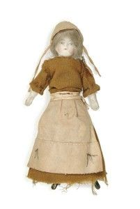 """This doll depicts a suffragette prisoner. The term """"suffragette"""" was used by the English militants to describe themselves.  The more moderate groups in England did not use the term. If you look carefully, you can probably see two upright arrows on the bottom of her apron, a symbol of Holloway Prison that all suffragettes were forced to wear.  This doll was probably dressed by a prisoner."""