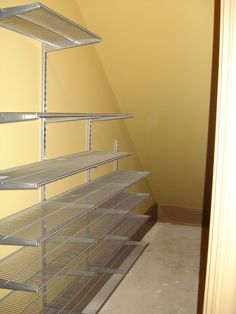 """The pesky under-the-stairs closet so may of us have. ELFA wall-mounted standards with 12"""" deep shelving does the trick!"""