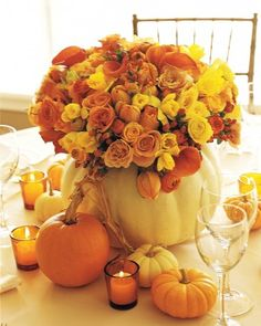 Pumpkin Centerpiece  A pumpkin shell becomes the vase for an arrangement of roses, daffodils, ranunculuses, calla lilies, tulips, and hypericum berries in fall colors -- yellows, peaches, and shades of orange. Smaller pumpkins and votive candles in orange-glass holders fill out the centrepiece - Martha Stewart