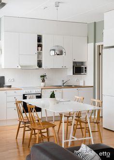 Yksinkertaisen valkoisen pöydän ympärille on kerätty lämpimän puun sävyiset tuolit. Kaunis valaisin on upea yksityskohta #keittiö #ruokailuryhmä #keittiöideoita #ruokapöytä #