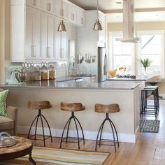 Pictured here a part of this kitchen counter-top scene are three of our extremely popular Henson Wood and Iron Swivel Counter Stools from designer Arteriors Home.