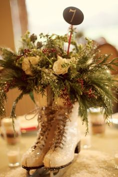 Vintage ice skates as a Christmas table centerpiece - centerpiece from real vintage ice skates filled with a mixture of greens, spray roses, larkspur, and burgundy seeded eucalyptus! spray the entire arrangement with glitter for a little glitz