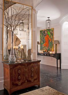 A contemporary entry hall maintains its minimalist aesthetic with limited holiday décor, like bare branches in a vase filled with silver ornaments - Traditional Home®