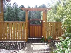I made the fence from rough cedar boards that I planed down to a smooth finish and installed with mortises. For the arbor I sheath the 4x4 redwood PT posts with cedar to keep the look. The gate...