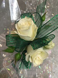 Wristlet corsage with white spray roses, emerald green ribbon, clear rhinestones…