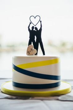 This gorgeous cake for with two grooms lights up the room.   #gayweddings #gayweddingideas #caketoppers  #gay