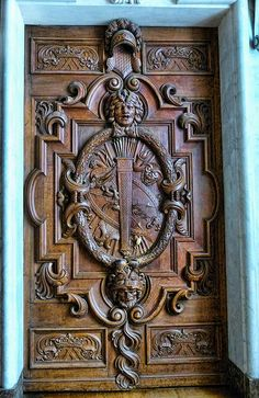 Ornate wood door featuring carvings of Medusa and Herakles in the Francois I Gallery at Fontainebleau