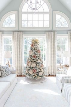 Soft pink Christmas Tree in light blue family room. Create a beautiful flocked tree with pink flowers and cream flowers and a hint of gold!