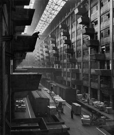"""Brooklyn Army Terminal - October 1949  //  """"Off-loaded freight from box cars being hoisted up to jutting loading platforms at Brooklyn Army Base.""""  Andreas Feininger photo, Life Magazine archives #brooklyn #industrial #navyard #interior #skylight #military"""