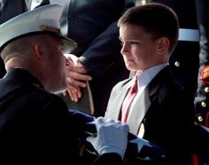 """Christian Golcznski, Child of a Fallen Marine From The Iraq War Receives  American Flag from Marine Lt. Col. Ric Thompson During a Military  Funeral for Staff Sgt. Marcus Golczynski"""