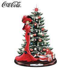 Inspired by art from actual COCA-COLA archives, this tabletop Christmas tree captures a Victorian-era lady dressed to the nines while enjoying a glass of COKE.  The fully sculpted tree is festively trimmed with red and white mini-lights, beaded-style garland, COCA-COLA ornaments, and more.