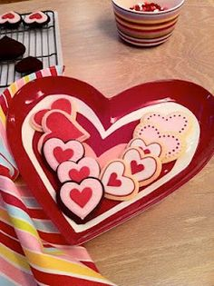 Confetti Cakes heart cookies (pipe small inner heart in royal icing, flood with royal icing and cover with sugar crystals. Allow to dry, then pipe the outer heart and flood the space between the two hearts in a complementary or contrasting colour)