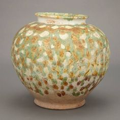 Chinese Sancai Glazed Pottery Jar Tang Dynasty The ovoid shape below a short neck and rolled rim, glazed with spotted amber, cream and green glaze all terminating above the foot. Height 7 7/8 inches.
