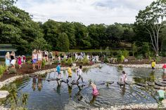 Children use stepping-stones to cross a man-made frog pond in the new Children's…