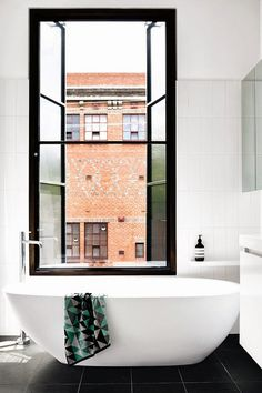 Black and white bathroom uses a crittall window as part of the main design feature.