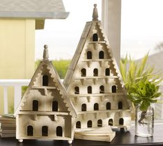 "Wood Bird House : decorative birdhouses of hand-carved mango wood, with gingerbread details and the arched openings of classic Victorian dove cotes. Ball feet, turned wood spires, weathered white painted finish. Large is 33""h x 21""w x 6""d / small is 22""h x 14""w x 6""d"