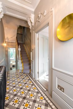 This grey and yellow themed hallway is stunning. A modern take on Victorian interiors.