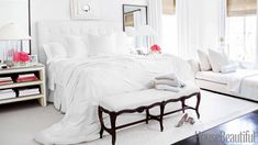 White walls, white rug, white bedding, and white bench, white headboard, white couch, white curtains, white lamps, and white nightstand