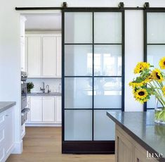 gorgeous barn door with modern hardware is located in a kitchen. The frosted glass lets in light but gives privacy to the utility kitchengorgeous barn door with modern hardware is located in a kitchen. The frosted gla.gorgeous barn door with modern Interior Sliding Barn Doors, Glass Barn Doors, Frosted Glass Barn Door, Modern Barn Doors, Sliding Door Design, Modern Sliding Doors, Steel Barns, Contemporary Barn, Kitchen Contemporary