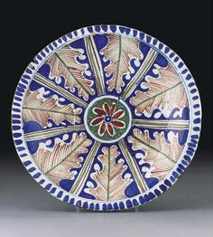 An English delft polychrome blue-dash charger  CIRCA 1710, probably Bristol  Painted with radiating iron-red oak leaves reserved on dark-blue panels, the centre painted with an iron-red and blue flowerhead on a mottled green circular cartouche, extending seven green and iron-red lines, within a blue-dash border  13 in. (33 cm.) diam.