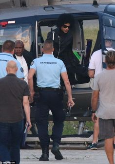 Seriously popular: Prince was greeted by security guards as he arrived on the Caribbean island via helicopter