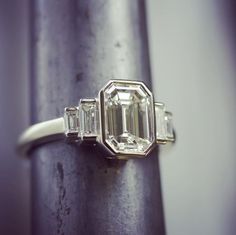 Hand-crafted 18k natural white gold engagement ring by Single Stone, named Caroline. A sleek design reminiscent of the Art-Deco era containing hand-set bezels. The center diamond features a beautiful