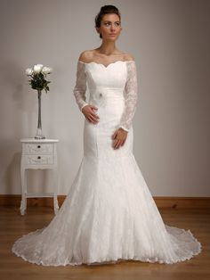 1505 - A slim classic lace gown with lace appliqué throughout. This timeless gown has a flattering sweetheart neckline and a pretty satin bow at the empire line. The full lace sleeves add another dimension to the beautiful design.