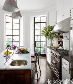 Kitchen of Boston designer, Nina Farmer whose gorgeous house is featured in the current issue of House Beautiful. It's classics and chic. You have all of the elements that have been so popular for the past several years-- carrera marble countertops paired with honed black granite, white cabinetry, a stainless La Cornue range, white subway tile backsplash, and Circa Lighting's Goodman Hanging Pendants by Thomas O'Brien.
