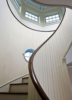 a serpentine staircase with beadboard walls and clerestory windows. Curved Staircase, Stair Railing, Staircase Design, House Staircase, Spiral Staircases, Staircase Ideas, Stair Steps, Beautiful Stairs, Beautiful Homes