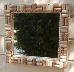 Upcycled Wine Corks Framed Mirror - An upcycled mirror created by lining the frame with used wine corks, some plain and some with Greek wine logos.  The frame has been enhanced by putting an exterior and interior rope trim - rope that was found on one of the local Skiathos beaches.  A piece of recycled mirror has been used for this piece.