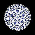 A fine Iznik blue and white pottery Dish.Turkey, circa 1570.Photo Bonhams with sloping cusped rim on a short foot, the...