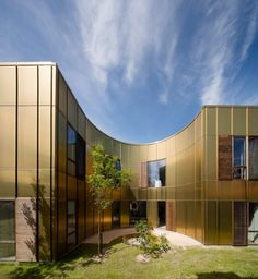 Golden facades and quiet curved courtyards feature in this hospice by Copenhagen studio NORD Architects .