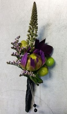 A purple groom's boutonniere with green hypericum accent features veronica, limonium, dahlia bud with a black satin wrap from Seasonal Celebrations.
