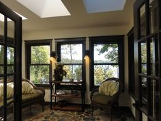 Sun-room faces south with velux skylight windows the perfect place to watch the lake sitting in the sun / screen room. Craftsman window trim adds appeal and the wall sconces between window frames creates ambiance. Sliced and polished field stone floor.