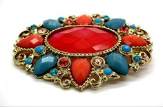 """Brooch, vintage with a stunning red center cabochon encrusted with multicolor rhinestones. Perfect condition.  ABOUT ME: I am a glamourous vintage brooch, encrusted with resin and glass gems in shade of red, blue and pink. MY MESURE: 2.5""""x2"""" TO TAKE OF ME: Just love, no water...and go party!  https://www.etsy.com/ca-fr/listing/199349292/broche-vintage-avec-un-cabochon-central?ref=listing-18&langid_override=0"""