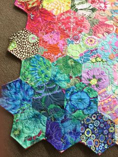 This quilt is made up of EPP hexagons, sewn together by hand and originally hand quilted but then i decided to throw it on the longarm and add some feathery texture to it.