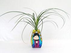 Floreros de cristal con acabado tipo vitral. Los hay en diferentes diseños:  Virgencitas,  cruces, mariposas, estrellas  y muchas  figuras más. Decóralos con plantas naturales o con flores artificiales.