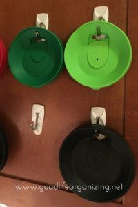 Use Command Hooks™ to hang cup lids on the inside of a cabinet door. | Good Life Organizing