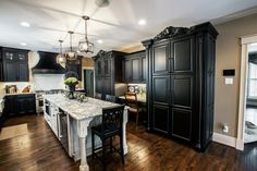 Gorgeous black and white kitchen with subway tile, hand-scraped hardwood flooring, granite countertops, farm sink, professional oven range and beautiful island.