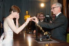 """Oscars 2013: Governors Ball after-party Supporting actress winner Anne Hathaway gets emotional while looking at her name on the engraved plate of her Oscar statue.   """"Les Miserables"""""""