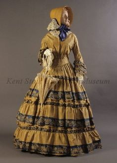 Gold coloured silk taffeta pleated, shirred front, pagoda sleeves, full skirt, 3 pinked ruffles with blue and mustard brocaded flowers, faux buttons at center back.