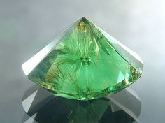 """Demantoid Garnet from Russia showing fine """"Horse-tail"""" like fibres of """"Byssolite"""" emanating from a tiny black chromite core."""