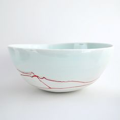 "porcelain bowl. approx 9"" wide, 5"" high. wheel thrown. glazed white and glassy blue, with red abstract drawing on the outside.food/microwave safe. handwash preferable.all items in this store are made in the wabi sabi tradition. crazing, crackling, and other irregular textures, marks and surfaces are part of the work."