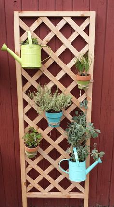 DIY Vertical herb garden.  Buy a trellis like this one for $10 - $15 @ lowes. Add some small pots, watering cans etc. with wire, cover with twine and your done.  Mason jars could be a nice addition. This took me a little less than an hour.