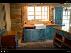 Neutral kitchen...pops of blue color. Love the wood cabin walls.